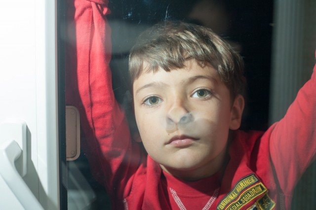 little boy looking through glass window