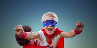 Criança com fantasia de super herói apoiada no ombro do pai faz movimento de voar